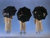 Three people in yellow raincoats with black umbrellas— their backs are turned in the picture.