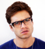 sebastian stan head cocked to the side wearing glasses looking slightly angry and slightly confused