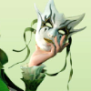A mask held by a hand with a green ruffled sleeve.