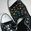 A pair of Black Converse with rainbow star shoelaces