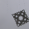 Square icon with dark grey, clouding sky in the background and a paper snowflake and raindrops on a glass pane in the foreground.