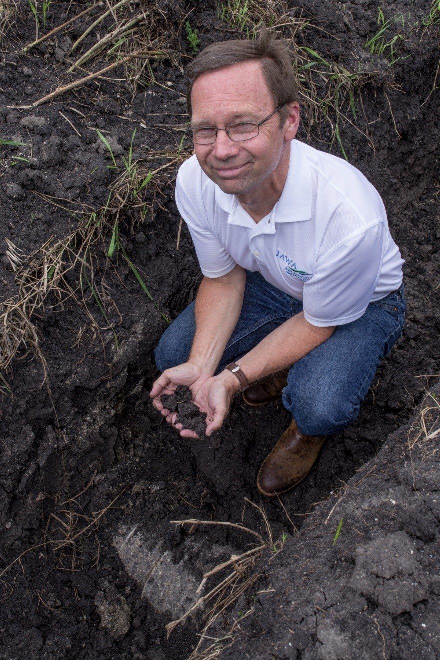 Jim Jordahl, Iowa Agriculture Water Alliance director of programs and operations, inspects a saturated buffer installation near Perry, Iowa.