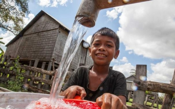 Boy at water tap in Cambodia. Timothy Herbert/Oxfam America.