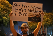 A man holds a sign reading DEAR FREE WORLD - ENJOY WATCHING US BURN