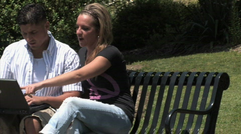 A young couple uses a wireless laptop outside in the park.