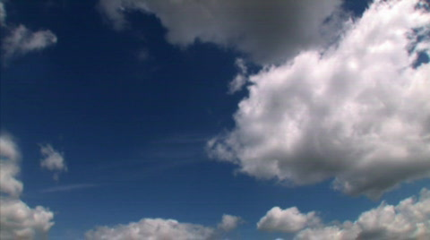 Time lapse of white puffy clouds in a deep blue sky.