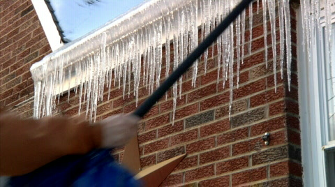 Breaking off dangerous hanging icicles from the roof.