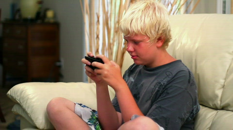 A young boy plays a handheld video game.