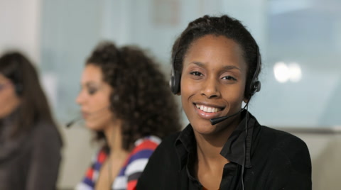 Panning on multiethnic group of female customer service representatives talking on the phone and looking at camera.