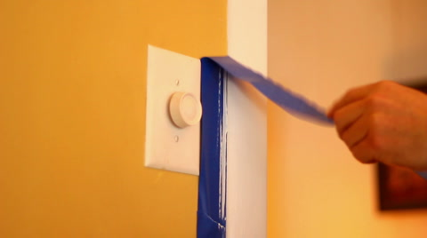 A painter removes blue painter's tape after painting trim in a house.  With audio.