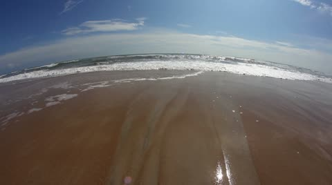 A fisheye look at the surf on a beach.