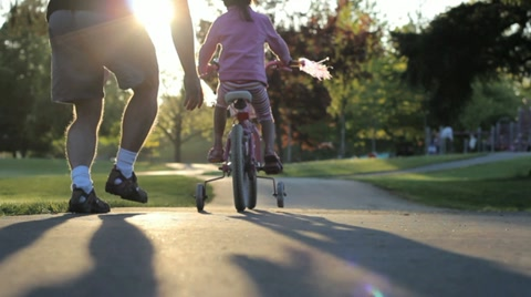 An excited dad helps her young Asian daughter ride her pink bike with training wheels up the hill to the playground.