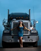 young pretty girl posing before huge cargo truck at night