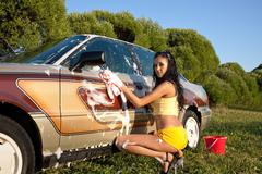 sexy woman washing a car at summer sunset - pin-up style
