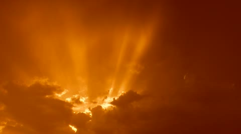 Time Lapse, Sun rays stream through clouds in bright, orange sky at sunset. 1080p