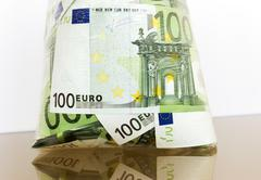 many hundred denominations of euro in a cellophane package on a reflecting surface