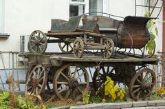 wooden carriage in front of an old biulding facade