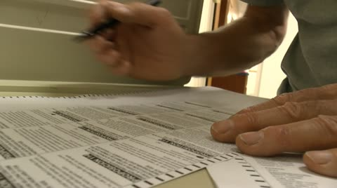 Man's hands, close up, voting, filling out ballot on election day in America. 1080p