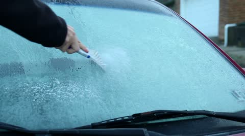 2802 Scraping off the ice on a car's windshield on a cold Winter morning.