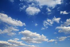 vertical image of blue sky with puffy white clouds