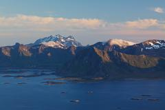 picturesque mountain range on lofoten islands in norway lit by midnight sun with tiny rocky islands in the sea