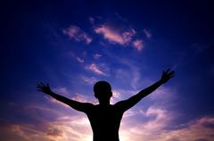 silhouette or backlit of asian man open arms raised towards sky on sunset