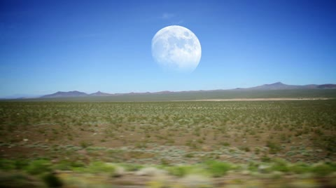 2911 Driving through the desert with the full moon in the distance.