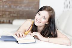 attractive young woman lying on her sofa with a book.
