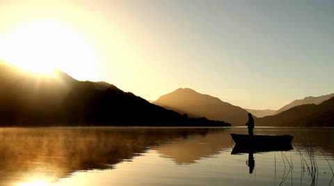 Silhouette of fly fishing fisherman casting from boat early in the morning, Golden background with mountains and lake.