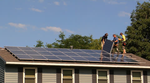 Workers installing solar panels on roof lay panel into place