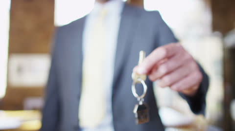 A key is held out with a shiny metallic key fob of a little house, symbolising the purchase of a new home. No faces can be seen.