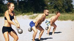 group doing crossfit workout on beach on a hot summer day