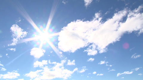 Blue sky day with bright sun shining bright with solar flare, time lapse.
