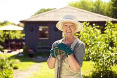 portrait of cheerful senior woman with gardening tools outdoors. older woman standing with shovel in her backyard garden