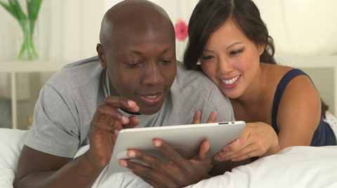 Close up dolly shot of African American and Asian couple using tablet pc in bed