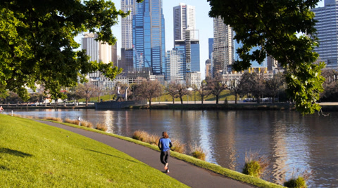 a woman runs along the banks of the yarra river in melbourne, australia