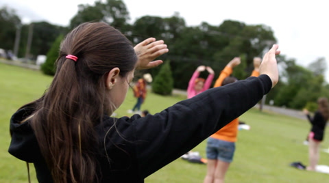 Young girl outdoors lifting arms and hands to Jesus