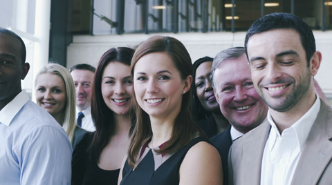 Portrait of a large business team. Content young business team smiling into camera.