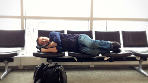 3969 A man rests at the gate at an airport.