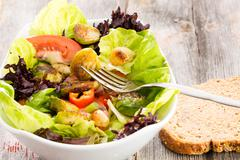 sauteed brussels sprouts in a mixed leafy green salad with tomato being eaten with a slice of fresh brown bread for an enjoyable light healthy lunchtime meal