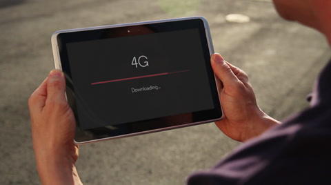 4163 A man downloads a file over 4G on his handheld tablet.