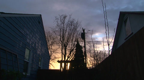 Sunrise time lapse in neighborhood with two houses bordering vivid cloudy sky.