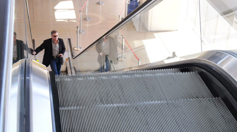 4172 A business man checks his cell phone while riding up an escalator.