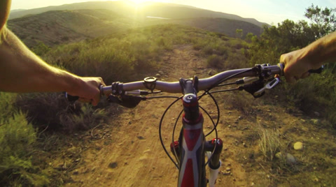Point of view shot of man mountain biking down dirt trail.