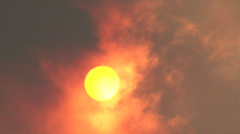 Red hot sun shines bright behind fast moving cloud of smoke.
