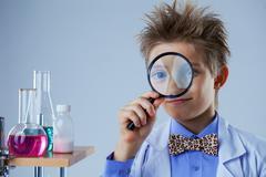 Portrait of curious boy looking through magnifier, close-up