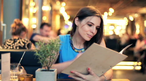 Young woman reading menu in restaurant HD