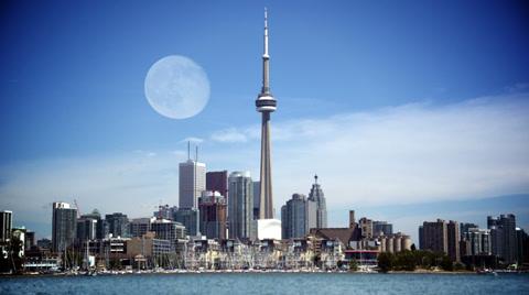 4651 TORONTO, ONTARIO, CANADA - Circa June, 2014 - An establishing shot of Toronto, Canada with a full moon above as seen from Lake Ontario.  Composited.