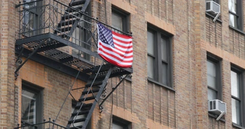 4693 An American flag hangs from the fire escape on a typical New York style apartment building establishing shot.