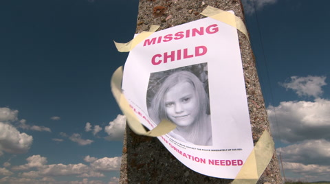 Missing person poster with photo of child are posted on pole